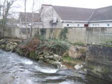 Scoured wall downstream of bridge